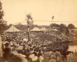 [European tightrope walker crossing a tank before a large crowd in Baroda.]